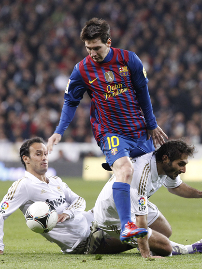 Faces and Places - 1.18.2012 The FC Barcelona's Argentine striker Lionel Messi (c) exceeds the Portuguese Carvalho (i) and Turkish Altintop, both Real Madrid during the first leg of the quarterfinals of the Copa del Rey which is being held tonight at the Santiago Bernabeu stadium in Madrid.