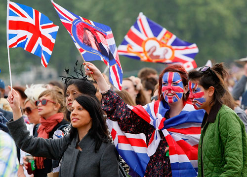Party in the U.K. - LONDON, ENGLAND - APRIL 29: Spectators wave their flags in Hyde Park where big screens have been set up to watch the wedding ceremony on April 29, 2011 in London, England. The marriage of Prince William, the second in line to the British throne, to Catherine Middleton is being held in London today. The Archbishop of Canterbury conducted the service which was attended by 1900 guests, including foreign Royal family members and heads of state. Thousands of well-wishers from around the world have also flocked to London to witness the spectacle and pageantry of the Royal Wedding and street parties are being held throughout the UK.