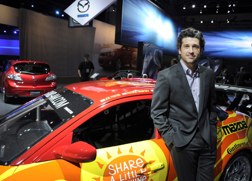 Faces and Places - 11.16.2011 The actor and American race car driver Patrick Dempsey (right) poses with the Mazda RX8 race car in the field of Auto Show 2011.