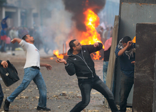 Faces and Places - 12.16.2011 Protesters throw stones at Egyptian security forces during a protest in Cairo, Egypt.