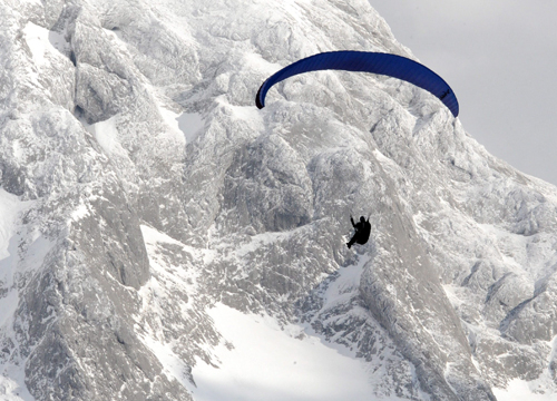 Faces and Places - 1.15.2012 A paraglider snowy passes near the Hohe Goell in Schoenau am Koenigssee, Bavaria (Germany).