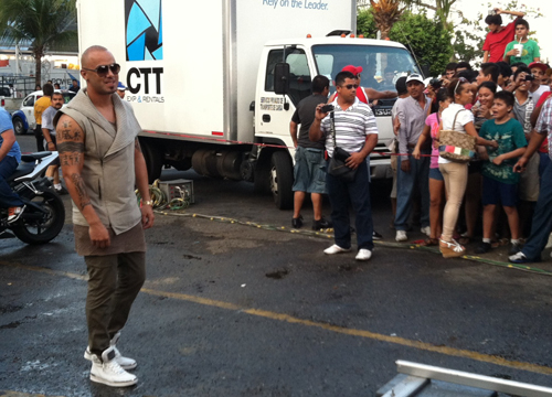 Follow the Leader: Behind the Scenes - Wisin poses for the camera while the crew sets up for the shoot. Looks like the excited crowd takes this opportunity to snap a few pics too. (We would!)